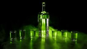 Flat surfaced bottle and six full shot glasses with vodka, tequila or sake against black background. Green smoke cloud fog