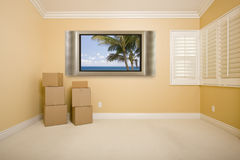 Flat Television on Wall in Empty Room with Boxes Stock Photo