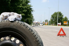 Flat tire. Car tire and a red triangle on the road Stock Photography