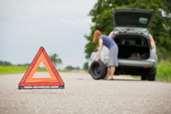 Flat tire on a car. A female driver about to fix a flat tire on her station wagon car. Focus on the warning triangle royalty free stock photos