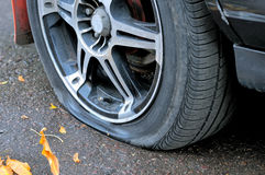 Flat tire of a car on the pavement. Side view close up Stock Images