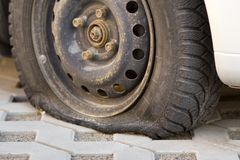 Flat tire of car on pavement. Side view outdoors of vehicle close up. Transportation problem, accident and insurance concept.  stock photography