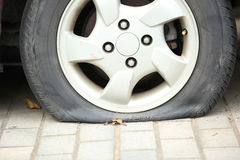 Flat tire on car wheel Stock Photos