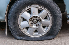 Flat tire. On concrete road Stock Photos