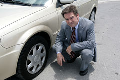 Flat Tire - Oh No. A businessman on the road with a flat tire.  He looks upset Royalty Free Stock Photos
