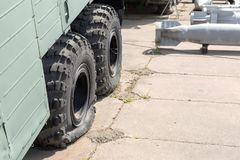 Flat tire of old military heavy truck. General-purpose air bombs on background. Army decay and degradation concept.  royalty free stock images