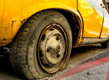 Flat Tire. Of an old yellow car with rusted rim Stock Photo