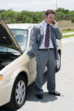 Flat Tire - Running Late. A businessman on the road with a flat tire.  He's calling his next appointment to say he will be late Stock Photography