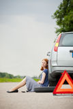 Flat tire and sad female driver Royalty Free Stock Photo