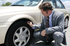Flat Tire with Screw. A businessman on the road with a flate tire.  He has just discovered the screw that caused the tire to go flat Stock Photography
