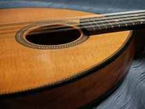 Flat-top Mandolin Side-View on Blue. Closeup view of a mandolin in old flatiron style; detail with herringbone trim, soundhole, and Koa wood sides. Photo taken Royalty Free Stock Photography