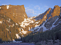 Flat top mountain from dream lake. Granite mountain peaks with snow in the valleys and pine trees in lower slopes bathed in orange morning light seen from shore stock photo
