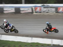 Flat Track Motorcycle Racing is a fast and exciting sport. Track racing is a form of motorcycle racing where teams or individuals race opponents around an stock images