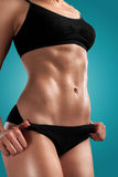 Flat tummy girl on blue. Royalty Free Stock Photography