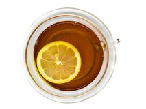 Flat view of tea in transparent, glass cup with floating lemon slice on white background stock photo