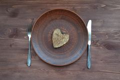 Flat view of wooden heart on plate. Romantic symbol. Dinner plate background. Valentine decoration. Wooden heart on plate. Romantic symbol. Dinner plate royalty free stock photography