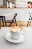 Flat white coffee with milk foam pattern on a white surface. Vertical Stock Photo