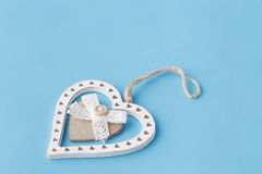Flat wooden heart on plain blue background Royalty Free Stock Image