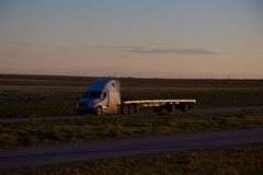 Flatbed Sunset. A White Freightliner Cascadia pulls an empty Flatbed trailer along a rural Us Highway during late sunset. All visible markings and trademarks stock photography
