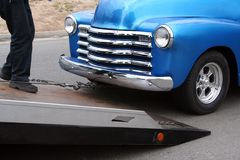 Flatbed tow truck hooks up a truck. A vivid blue classic American pickup truck is being attached to a flat bed tow ramp (truck) to be hauled away Stock Photo
