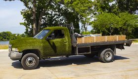Flatbed truck with artificial turf glued on the cab and wooden sideboards parked in street in front of trees and river stock photo