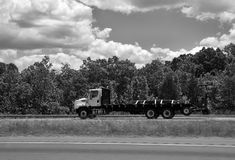 Flatbed Truck with Cargo on Open Road. Open flatbed truck is transporting cargo one the highway against trees and a cloud filled sky in black and white royalty free stock photo