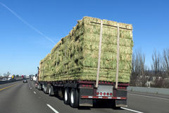 Flatbed Truck Freight. Flatbed truck with cargo of hay on highway Royalty Free Stock Image