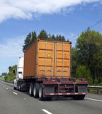 Flatbed Truck with Shipping Container. Orange shipping container being transported on flatbed semi truck Royalty Free Stock Photography