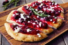 Flatbread appetizer with cranberries and goat cheese, on serving board Royalty Free Stock Images