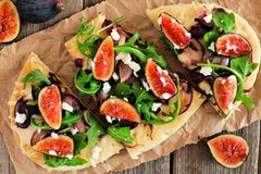 Flatbread with figs, arugula, caramelized onions and cheese, overhead scene. Flat bread pizza with figs, arugula, caramelized onions and cheese, overhead scene Stock Photo