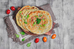 Flatbread Paratha roti. Stack of not sweet frying flour Flatbread Paratha roti, tortillas, cherry tomatoes, lettuce, napkin of burlap with lace, wooden board royalty free stock image
