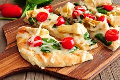 Flatbread pizza with mozzarella, tomatoes, spinach and artichokes, close up Stock Photo