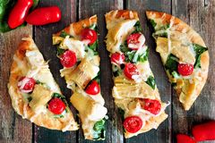 Flatbread pizza with mozzarella, tomatoes, spinach, artichokes, over rustic wood Royalty Free Stock Photography
