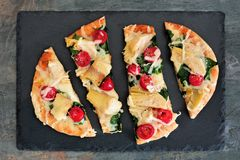 Flatbread pizza with mozzarella, tomatoes, spinach and artichokes on slate Stock Image