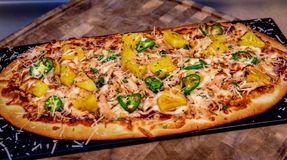 Flatbread Pizza with Pineapple and Jalapeños. Cooked flatbread pizza with pineapple and jalapeños Stock Photography