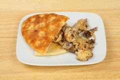 Flatbread and shitake mushrooms. Fried shitake mushrooms with focaccia flatbread on a plate on a wooden tabletop royalty free stock photography