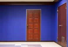 Flatdeur en blauwe muur Stock Fotografie