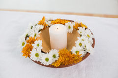Flate full of flowers and a lit candle Stock Photography