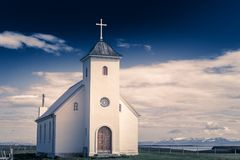 Flateyjarkirkja white lutheran church with meadow in foreground Royalty Free Stock Images