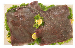 Flatfish. On marble plan with salad and lemon Royalty Free Stock Photos