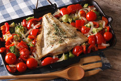 Flatfish with vegetables close-up on a frying pan. Horizontal. Flatfish with vegetables close-up on a frying pan on the table. Horizontal Royalty Free Stock Photo