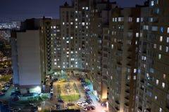 Flatgebouw in avondtijd met licht in vensters op voorgevel Royalty-vrije Stock Afbeeldingen
