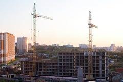 Flatgebouwplaats en kranen in de stad in zonsopgang royalty-vrije stock foto's