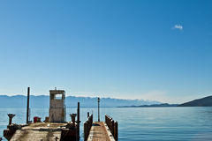 Flathead Lake Dock w/ Barge. Bluebird sky over Flathead Lake dock and construction barge with mountain background Royalty Free Stock Photography