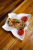 Flathead lobster fried with garlic. Served with tomato slices in local port restaurant. Traditional thai seafood cuisine made of fresh ingredients Royalty Free Stock Photography