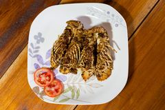 Flathead lobster fried with garlic. Served with tomato slices in local port restaurant. Traditional thai seafood cuisine made of fresh ingredients Royalty Free Stock Photos