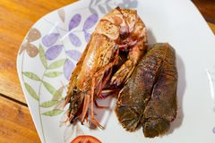 Flathead lobster and giant prawn. Flathead lobster fried with garlic and grilled giant prawn served with tomato slices in local port restaurant. Traditional thai Stock Photos