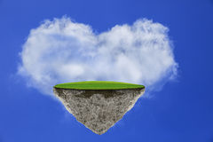 Flating island with green grass field on blue sky against heart shape cloud Stock Photos