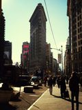 Flatiron Building From Broadway. Flatiron building photographed from Broadway pictured in low winter sun whilst city dwellers walk by casting long silhouettes Stock Photos