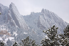 Flatiron Rocks Mountain Snowy Scenic. Foothills of the Mountains. Flatiron rocks covered in snow with pine trees. Winter scenic postcard Stock Photography